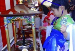 (上)雅楽の音色に包まれながらの行列。 (下)誕生仏に甘茶を濯ぐ子供たち。